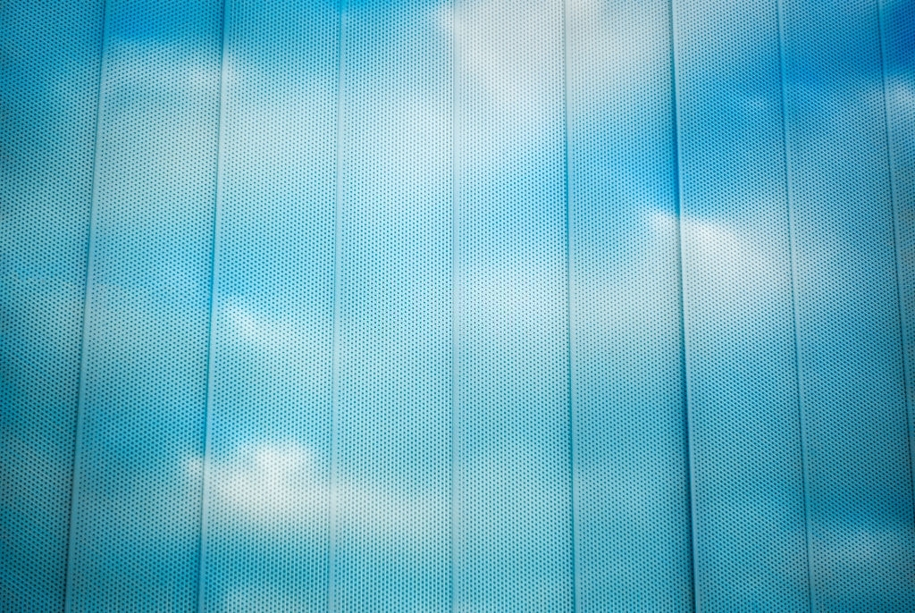 Clouds and sky reflecting in window with window shades